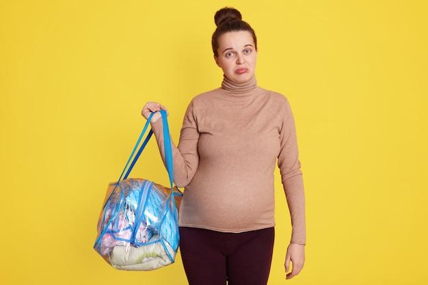 Donna incinta in posa contro il muro giallo con le labbra imbronciate, preoccupata prima di andare a casa di maternità, in piedi con la borsa con le sue cose in mano, che indossa un maglione casual e leggins.