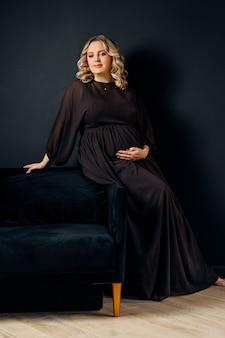 Donna incinta posa in un elegante abito nero al chiuso studio sfondo muro nero bionda indoeuropea mezza età femmina gravidanza di sei mesi