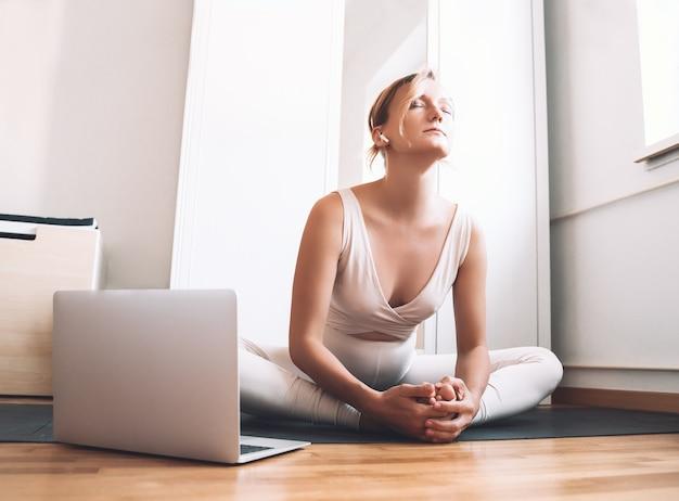 Donna incinta che pratica yoga a casa con il computer portatile l'esercizio femminile medita durante la gravidanza