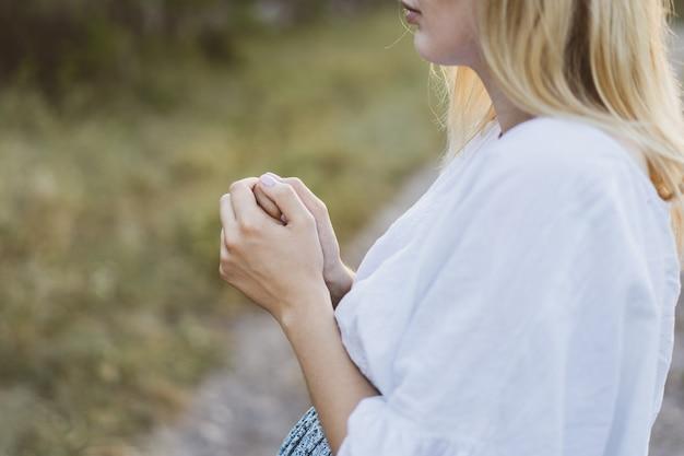 Donna incinta che prega all'aperto al tramonto. concetto di fede, spiritualità e religione. pace, speranza