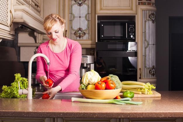 La donna incinta ha preparato una cena in cucina. mangiare sano concetto. focus sulla ciotola con le verdure