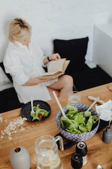 Donna incinta che legge un libro mentre mangia