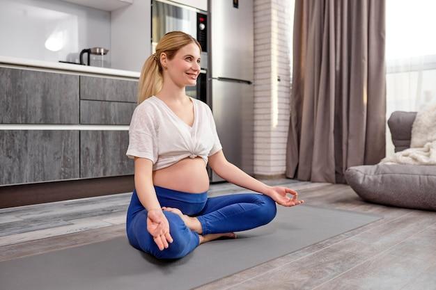 Donna incinta che si siede nella posizione del loto sul pavimento pronto per l'esercizio prenatale di yoga