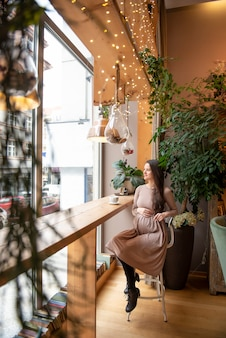 Donna incinta che si siede con la tazza di tè dentro il caffè