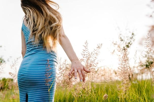 Donna incinta stare in erba all'aperto, in un campo con i fiori alla luce del sole.