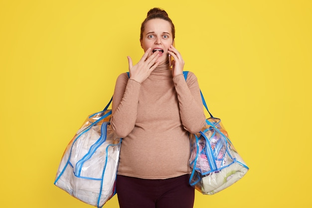 La donna incinta in piedi isolata sopra il muro giallo per consegnare all'ospedale, si sente preoccupata e ha paura, tiene la bocca aperta, copre le labbra con i palmi, ha paura di partorire.