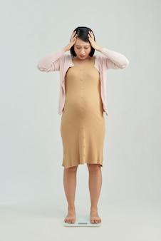 Donna incinta in piedi su una bilancia