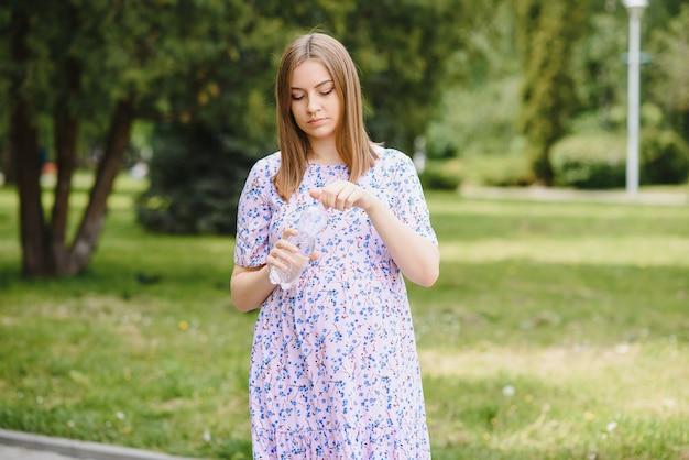 La donna incinta sta nel parco con una bottiglia d'acqua