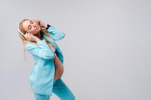 Una donna incinta in un abito turchese con le cuffie sta in piedi e ascolta musica su uno sfondo grigio