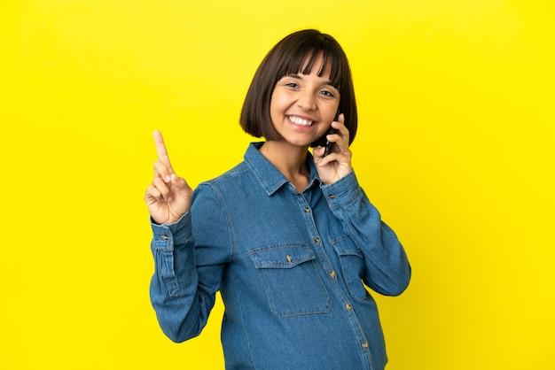 Donna incinta che utilizza il telefono cellulare isolato su sfondo giallo che indica una grande idea