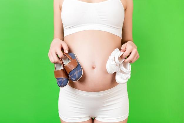 Donna incinta in biancheria intima bianca che tiene scarpe per bambini