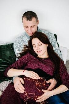 La donna incinta, la cui pancia è decorata con lucciole, l'uomo la abbraccia. buon natale. interno decorato di natale. gravidanza, vacanze in famiglia, persone e concetto di aspettativa.