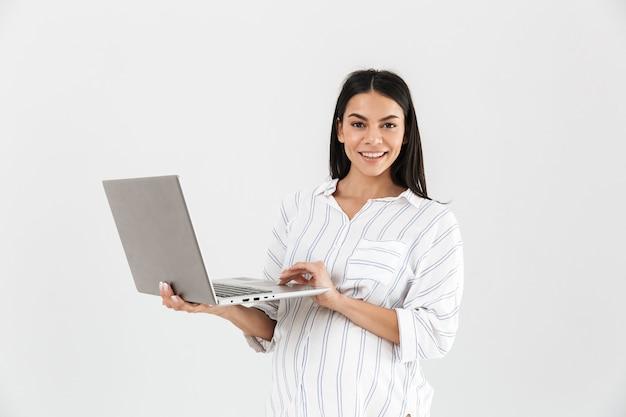 Donna incinta con la grande pancia che sorride e che tiene il computer portatile nelle mani mentre levandosi in piedi isolato sopra il muro bianco