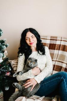 Donna incinta con gatto vicino all'albero di natale a casa vacanze in gravidanza e concetto di aspettativa
