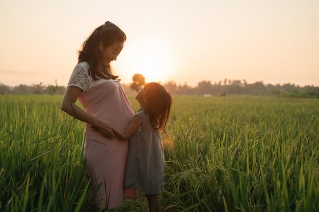 Donna incinta con sua figlia godendo all'aperto