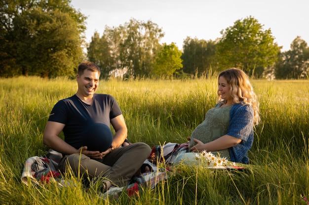 Una donna incinta con il marito su uno sfondo di un campo