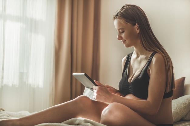 Donna incinta con tablet moderno seduto sul letto e aggiustandosi i capelli lunghi