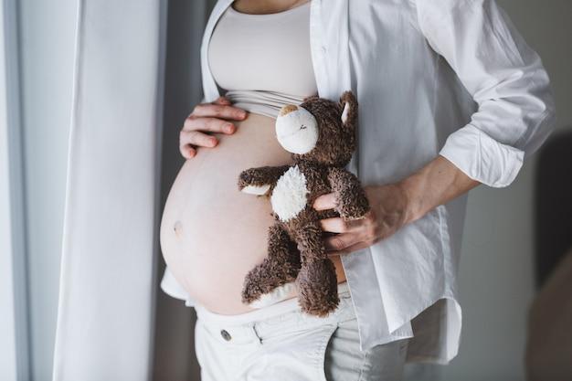 Donna incinta con il bambino in ascolto dell'orsacchiotto del giocattolo