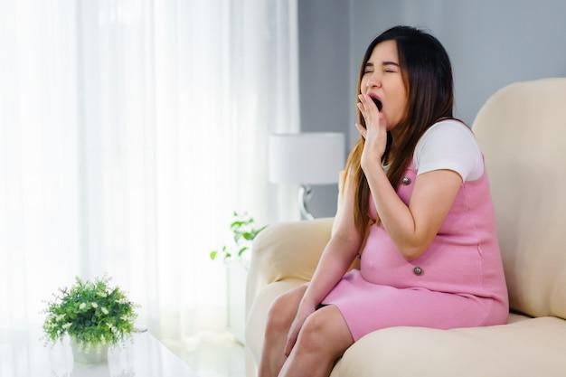 Donna incinta che sbadiglia e che dorme sul divano del soggiorno