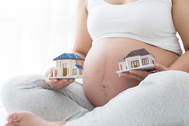 Prestito domestico selezionato delle donne incinte, comprante una casa durante il concetto di gravidanza