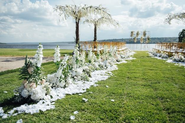 Arco premium per cerimonia nuziale per sposi novelli sulla riva del fiume con alberi di glicine. sedie e ombrelloni vuoti