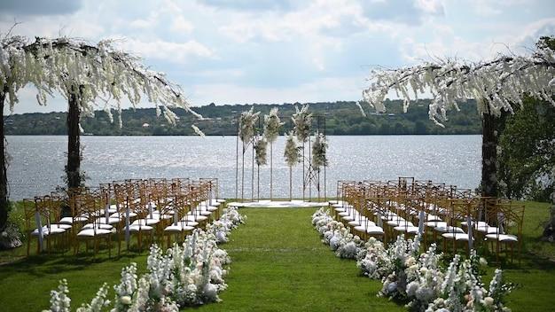 Arco premium per cerimonia nuziale per sposi novelli in riva al fiume con alberi di glicine