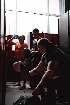 Preparazione ai pugili degli atleti di grande combattimento in abbigliamento sportivo che preparano i guantoni da boxe per l'allenamento in
