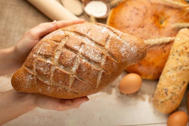 La preparazione di pane, pane fresco in primo piano delle mani su fondo di legno vecchio, concetto per la cottura