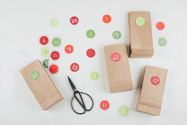 Preparazione del calendario dell'avvento natalizio. sacchetti di carta ecologici con regali per bambini. natale sostenibile. disposizione piatta, vista dall'alto