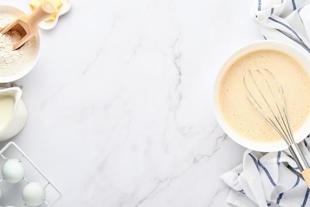 Preparazione dell'impasto per le frittelle fatte in casa per gli ingredienti della colazione sul tavolo