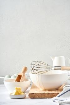 Preparazione dell'impasto per frittelle casalinghe per colazione o per maslenitsa. ingredienti sulla tavola farina di frumento, uova, burro, zucchero, sale, latte