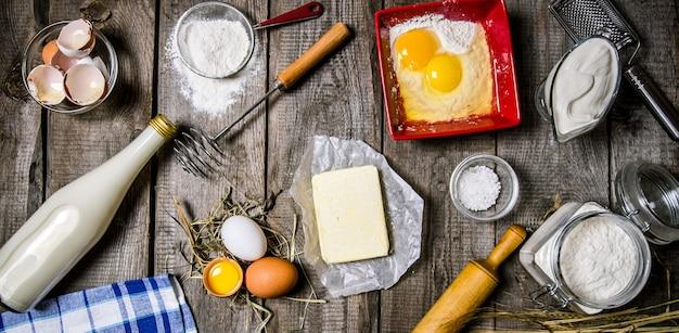 Preparazione dell'impasto. ingredienti per l'impasto: latte, panna, burro, farina, sale, uova e diversi strumenti. su un tavolo di legno. vista dall'alto