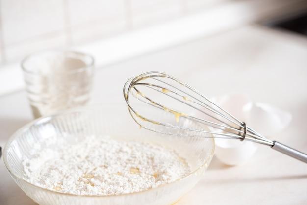 Preparazione dell'impasto una misura della quantità di ingredienti nella ricetta. ingredienti per l'impasto: farina, uova, mattarello, frusta, latte, burro, panna. Foto Premium