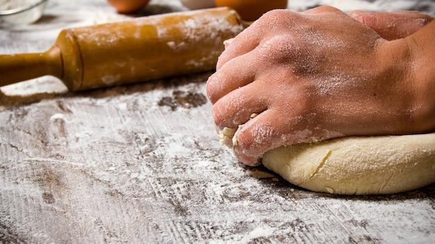 Preparazione dell'impasto. preparazione dell'impasto le mani delle donne. su un tavolo di legno.