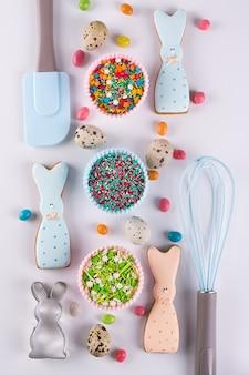 Preparazione di biscotti di panpepato di pasqua. tagliabiscotti, biscotti a forma di coniglietto divertente e utensili da cucina