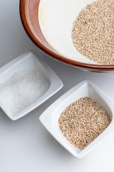 Preparazione del gomashio (condimento gomasio - sekihan) con semi di sesamo e sale in suribachi (malta a strisce giapponesi)