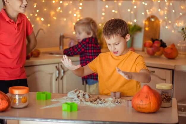 Preparazione per la festa di halloween. tre allegri bambini fanno i biscotti in cucina