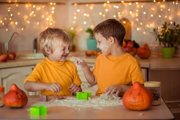Preparazione per la festa di halloween. due bambini allegri fanno i biscotti in cucina