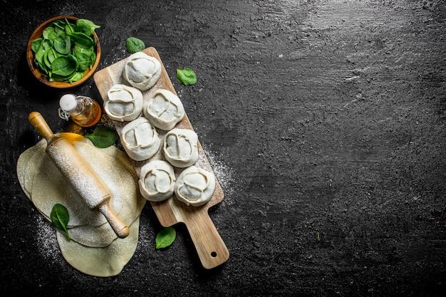 Preparazione gnocco di manta crudo fatto in casa con foglie di spinaci sul tavolo rustico