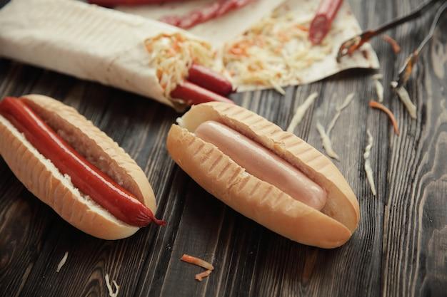 Preparazione di hot dog con salsiccia.foto su uno sfondo di legno.