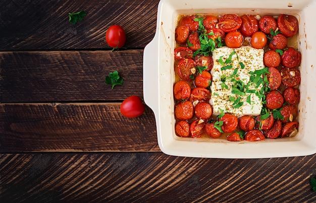 Preparazione degli ingredienti per fetapasta. ricetta di pasta al forno feta di tendenza a base di pomodorini, formaggio feta, aglio ed erbe aromatiche. vista dall'alto, sopra, copia dello spazio.