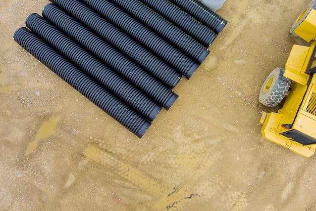La preparazione per l'installazione lavora i tubi di plastica in pvc che giacciono a terra sul cantiere