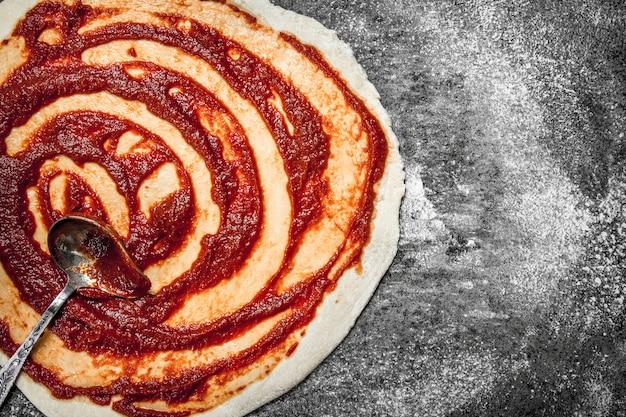 Preparazione della pizza. applicazione della salsa di pomodoro sulla pasta arrotolata sul tavolo rustico.
