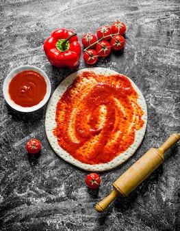 Preparazione pizza. pasta stesa con diversi ingredienti per pizza. su fondo rustico