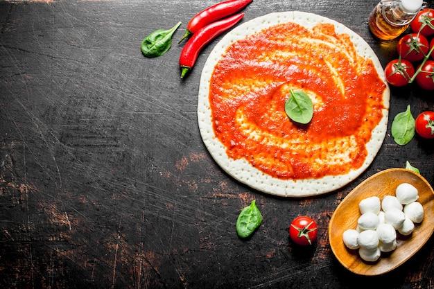Preparazione pizza. pasta stesa con concentrato di pomodoro, peperoncino e mozzarella. su fondo rustico scuro