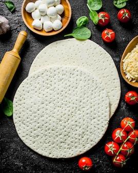Preparazione pizza. pasta rotonda con pomodori, formaggio e spinaci. su sfondo nero rustico