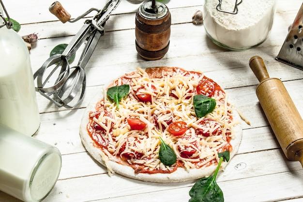 Preparazione della pizza con vari ingredienti. su un tavolo di legno bianco.