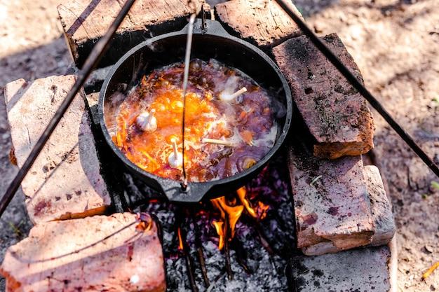 Preparazione del pilaf armeno radizionale in un calderone su un fuoco aperto.