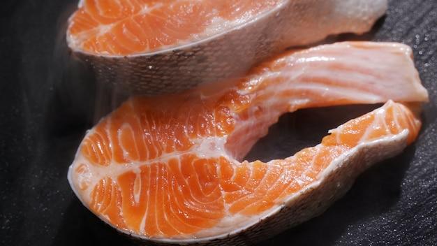 Preparazione del trancio di salmone speziato e sale cosparso su un pezzo di salmone crudo