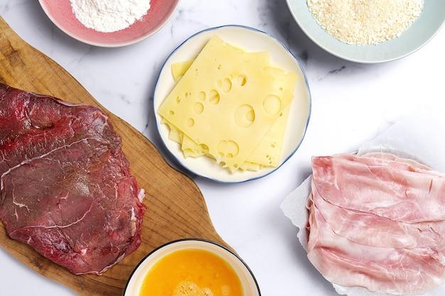 Preparazione della tradizionale scaloppina di vitello milanesa fatta in casa con farina, uovo, pangrattato, formaggio e prosciutto